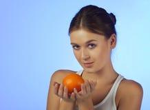 La mujer con una fruta anaranjada Imágenes de archivo libres de regalías