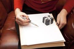 La mujer con una hoja limpia de papel especifica Imagen de archivo libre de regalías