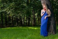 La mujer con una manzana cerca de un árbol Imágenes de archivo libres de regalías