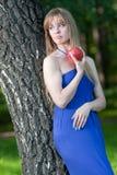 La mujer con una manzana cerca de un abedul Imagen de archivo libre de regalías