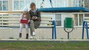 La mujer con una ni?a se est? sentando en un banco y est? utilizando los artilugios almacen de video