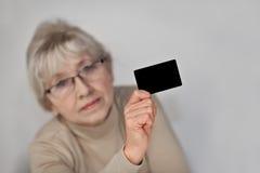 La mujer con una tarjeta plástica Imagenes de archivo