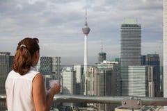 La mujer con una taza de café en el último piso de un rascacielos admira la opinión Kuala Lumpur Fotos de archivo