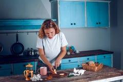La mujer concentrada corta el limón en tabla de cortar en la cocina fotos de archivo