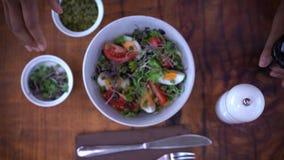 La mujer condimenta una ensalada fresca hecha con lechuga, tomate, huevos y aceitunas Semillas de calabaza, brotes de alubias y s metrajes