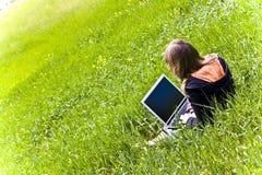 La mujer conectó en la hierba Fotografía de archivo