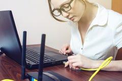 La mujer conecta el cable de Internet con el conector en el ordenador portátil Imagen de archivo