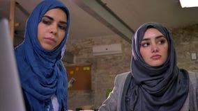 La mujer confiada concentrada en hijab azul se está sentando con su colega musulmán, señalando la mano en una pantalla, woking almacen de metraje de vídeo