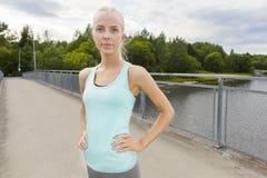 La mujer confiada se coloca en el puente después de entrenamiento Imágenes de archivo libres de regalías