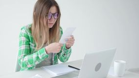 La mujer considera la cantidad de costos para las compras y el pago de créditos incorporando la información en el ordenador portá almacen de metraje de vídeo