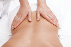 La mujer consigue detrás masaje Imagen de archivo libre de regalías
