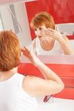 La mujer consigue la crema en cara Foto de archivo