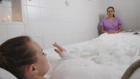 La mujer controla el balneario hidráulico del baño del masaje, haciendo al cliente del masaje que miente en el baño El operador d almacen de metraje de vídeo