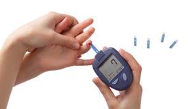 La mujer controla el nivel de la glucosa en sangre en el niño fotos de archivo libres de regalías