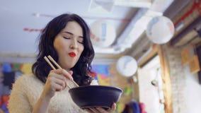 La mujer coreana hermosa goza del plato coreano tradicional y muestra el pulgar para arriba almacen de video
