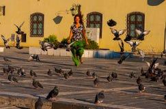 La mujer corre abajo de la calle a través de una multitud de palomas Fotos de archivo