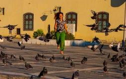 La mujer corre abajo de la calle a través de una multitud de palomas Fotos de archivo libres de regalías