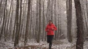 La mujer corre en la madera del invierno La mujer hermosa en una chaqueta brillante para jugar deportes en la madera Forma de vid almacen de metraje de vídeo