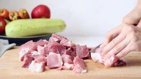 La mujer corta la carne de cerdo en una tabla de cortar para la carne asada metrajes