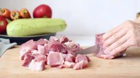 La mujer corta la carne de cerdo en una tabla de cortar para la carne asada almacen de video