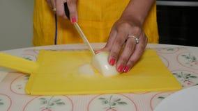 La mujer corta cebollas en una tabla de cortar y las vierte metrajes