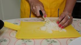 La mujer corta cebollas en una tabla de cortar y las vierte almacen de video