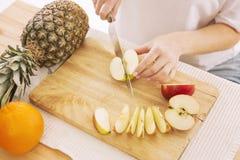 La mujer corta la fruta en rebanadas en una tabla de cortar imagen de archivo