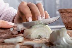 La mujer corta la cebolla en rebanadas Foto de archivo libre de regalías
