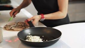 La mujer corta lentamente la cebolla en cuadritos en la tajadera de madera en cocina almacen de metraje de vídeo