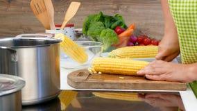 La mujer corta maíz en la cocina metrajes
