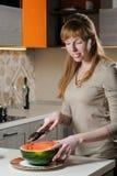 La mujer corta una sandía en la cocina fotografía de archivo