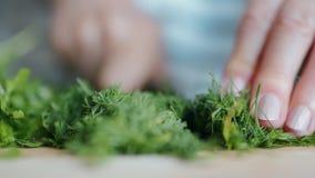 La mujer corta verdes frescos en una tabla de cocina Ciérrese encima de la cámara lenta almacen de metraje de vídeo