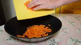 La mujer corta zanahorias en la tabla de cortar almacen de video