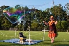 La mujer crea las burbujas enormes de Coloful en Georgia Festival Foto de archivo