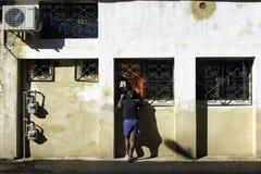 La mujer cubana mira en una ventana de la calle Imagen de archivo libre de regalías