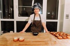 La mujer cuece las empanadas Los confiteros hacen los postres Fabricación de los bollos Pasta en la tabla fotos de archivo libres de regalías