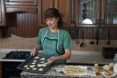 La mujer cuece las galletas en la cocina Imagen de archivo libre de regalías