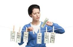 La mujer cuelga moneda en la línea Imágenes de archivo libres de regalías