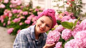 La mujer cuida para las flores rosadas en casa de campo Concepto de cuidado para las flores Brotes enormes increíble hermosos del almacen de video
