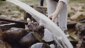 La mujer da la botella de relleno del wellspring del agua dulce en bosque almacen de video