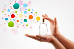 la mujer da burbujas coloridas de rociadura de la botella de perfume hermosa imagenes de archivo