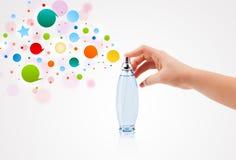 la mujer da burbujas coloridas de rociadura de la botella de perfume hermosa Imagen de archivo
