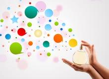 la mujer da burbujas coloridas de rociadura de la botella de perfume hermosa Fotografía de archivo libre de regalías
