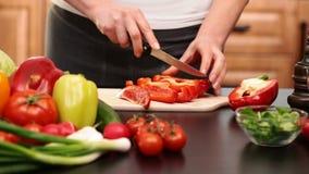 La mujer da cortar el paprika rojo para una ensalada de las verduras