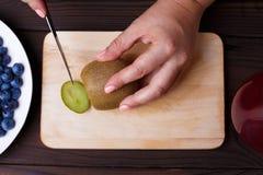 La mujer da cortar un kiwi para la placa de la fruta, visión superior TA orgánica foto de archivo libre de regalías