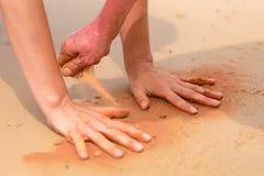 La mujer da crear formas con la arena roja en la playa en estilo aborigen del arte Imagenes de archivo