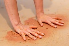 La mujer da crear formas con la arena roja en la playa en estilo aborigen del arte Fotografía de archivo libre de regalías