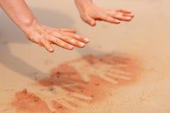 La mujer da crear formas con la arena roja en la playa en estilo aborigen del arte Imagen de archivo