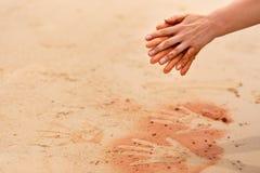 La mujer da crear formas con la arena roja en la playa en estilo aborigen del arte Imagen de archivo libre de regalías