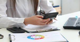 La mujer da la cuenta en la calculadora y documentos de relleno en oficina moderna almacen de metraje de vídeo